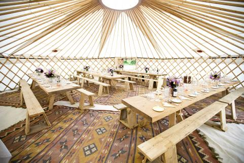 32ft yurt with simple decor and rustic tables