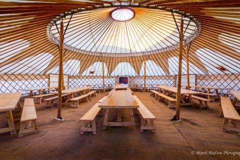 44ft yurt with simple decor and banqueting tables for 120